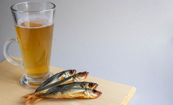 Smoked horse mackerel and beer in a glass on a wooden board on a gray background. Oktoberfest Holiday Concept.