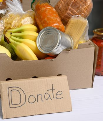 cardboard box with various products, fruits, pasta in a plastic bottle and preservation