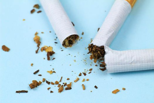 Broken cigarette on blue background. Stop smoking concept photography.