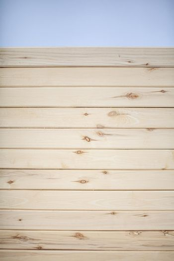 The background is a wall made of wooden beams.Texture for your design. Wooden beam and board. Background for still life. Beautiful wood texture.