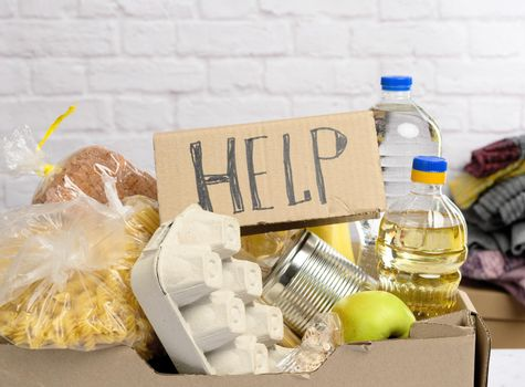 cardboard box with various products, fruits, pasta, sunflower oil in a plastic bottle and preservation