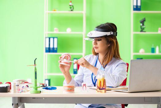 Woman dentist working on teeth implant