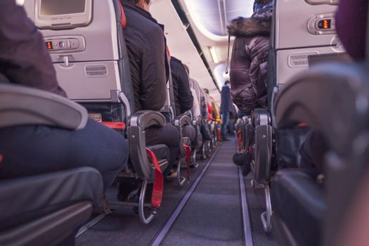 airplane seats low angle view and legs and shoes of passengers sitting