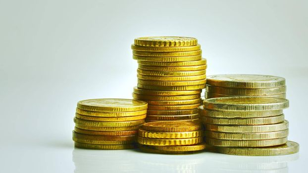 Dollar and Thai baht coins are stacked separately on white background, copy space available.