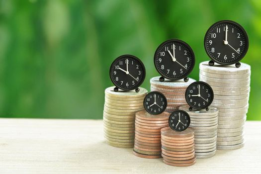 Abstract Alarm Clock and Coins stacked on your desk, time for savings ideas, banking and business concepts and with nature background.