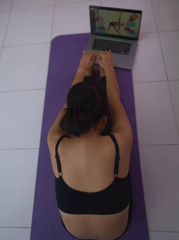 A young woman doing exercise as a model from an online course on her laptop