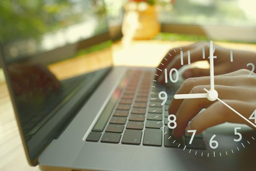 An abstract hand typing a laptop and an analog clock showing the start time of the workplace.