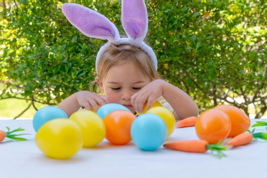 Cute Little Baby Dressed as Bunny Playing with Nice Colorful Eggs. Traditional Easter Decorations. Spring Christian Holiday