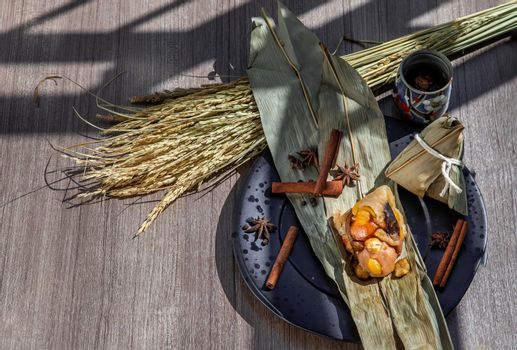 Chinese rice dumpling shaped pyramidal wrapped by leaves ingredients on dried banana leaf.