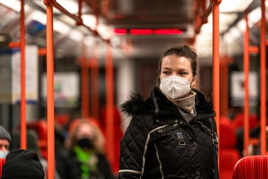 woman in public transport with a respirator on her face. coronavirus epidemic