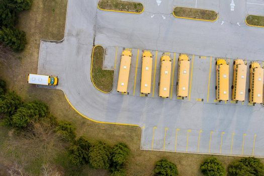 Yellow school buses in parked the parking lot of the day