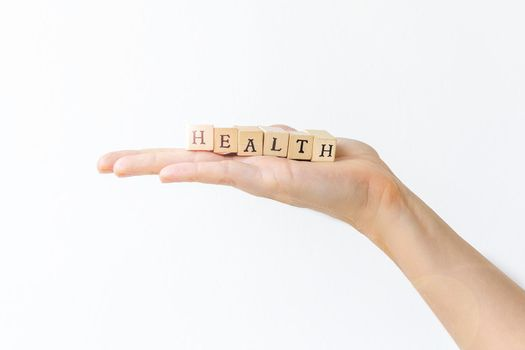 Hand holding wooden letters for health concept. White background.
