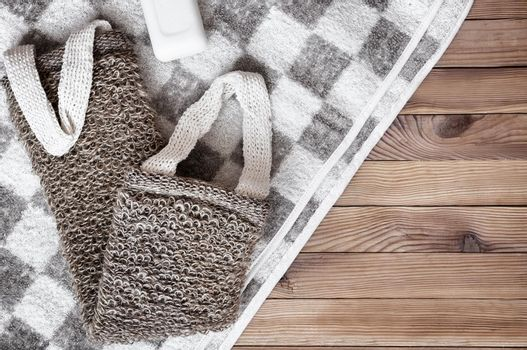 Accessories for visiting the bath or sauna on a wooden background: towel, washcloth. Top view with copy space. Flat lay