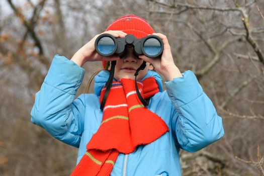 A girl looks through binoculars on a background of a winter forest, front view, close-up