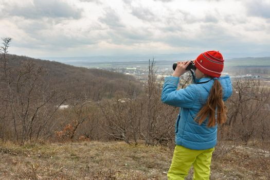 A girl examines a mountain landscape through binoculars, view from the back