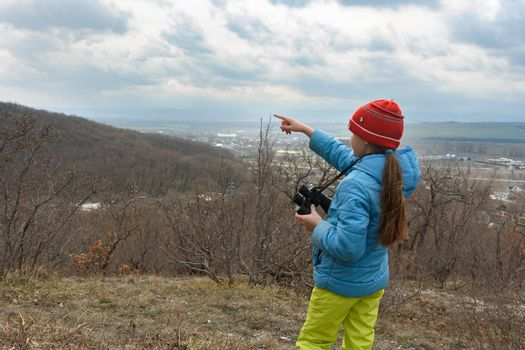 The girl saw something through binoculars, looking at the mountains and points there with her finger