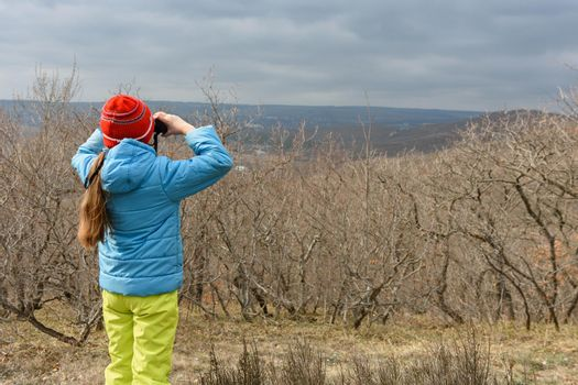 A girl in an autumn day looks through binoculars from the mountain, back view
