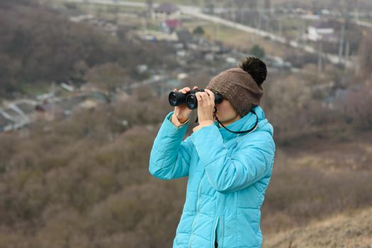 Girl looking through binoculars while standing on top of a mountain on a warm autumn day