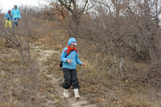 A girl runs down the path from the mountain, in the background a girl with another girl gently descend from the mountain