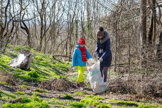 Family collects trash in the forest in a big bag for recycling