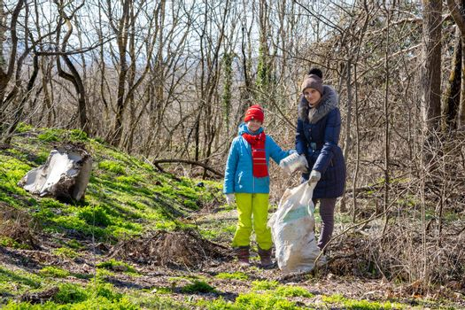 A girl and her daughter collect garbage in the forest in early spring, they looked into the frame