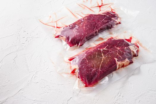 Set of vacuum packed organic beef meat rump steak on white concrete textured background, side view space for text.