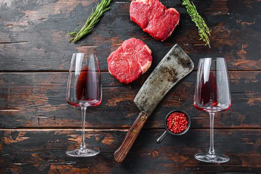 Raw rump steaks with american butcher cleaver and two glass of red wine over dark old wooden background, top view space for text