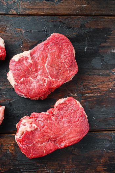 Variety of organic raw beef steakes rump cut on old rustic dark wooden background, top view.
