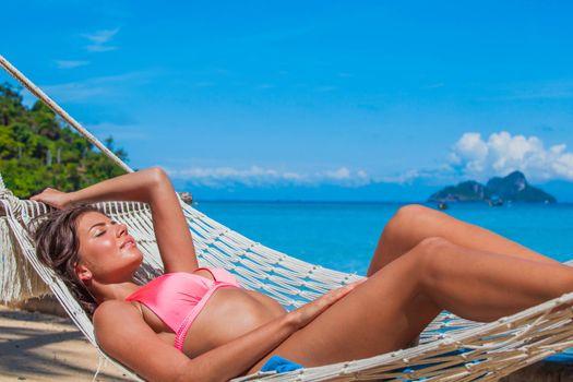 Girl in bikini relaxing in hammock on the beautiful paradise beach