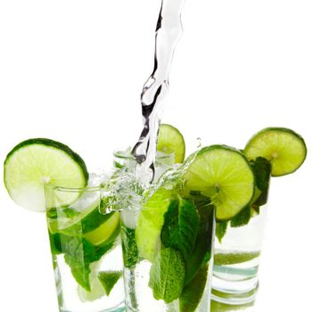 Making mojito cocktails with lime and mint isolated on white background