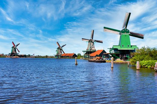 ZAANSE SCHANS, NETHERLANDS - CIRCA AUGUST 2020: Dutch windmill in green countryside close to Amsterdam, with blue sky and river water.