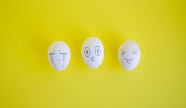 White eggs with funny faces on a yellow background. Easter Concept.