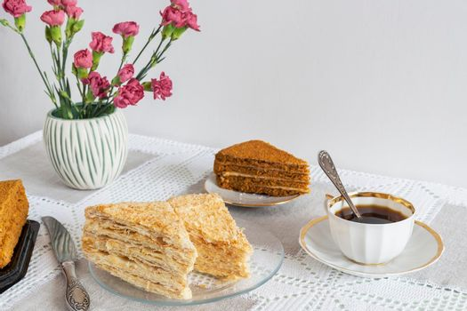 Alternative coffee substitute: a hot decaffeinated drink made from natural chicory, on the table in a white cup. Next to a delicious cake and flowers. Front view with copy space.
