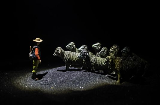 Sheep in the farm. Group of sheep silhouettes at the field. Decorative toy figures at night. Selective focus