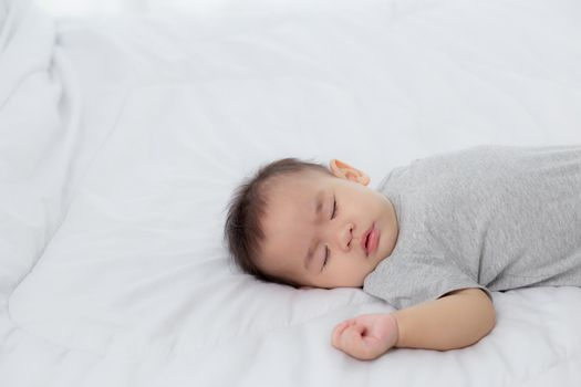 Portrait of asian little baby girl sleeping on bed in the bedroom at home, newborn napping with cozy and relax, infant innocence in bedtime, happy toddler cute, growth of child and emotion, indoors.