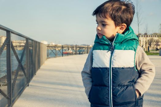 Portrait of little boy wearing sleeveless jacket, child looking away from camera, stands on promenande along river.