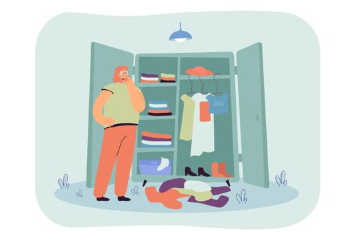 Thoughtful woman choosing clothes in wardrobe