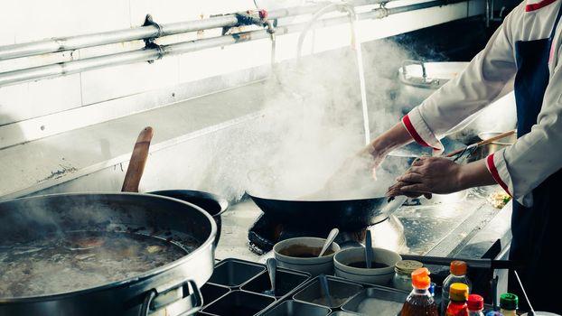 Chef stir fry in wok.