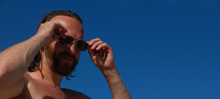 Close up portrait of mid adult man in sunglasses with wet hair on the beach seaside vacation male skincare concept