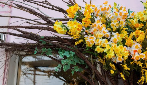 The shop is decorated with bright, artificial flowers, daffodils and branches. A fragment of a building decorated with flowers.