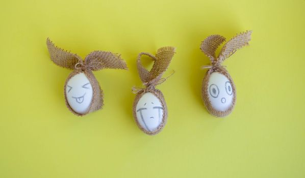 White eggs with funny faces in sackcloth on a yellow background. Easter Concept.