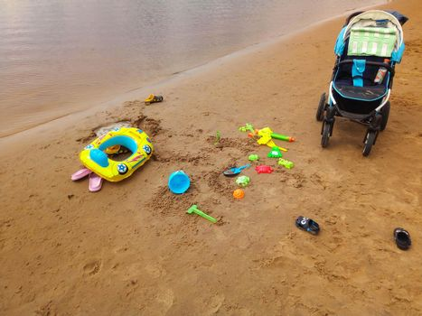 The concept of a beach holiday for children. Baby stroller and bright plastic children's toys in the sand. Space for text.