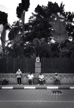 2019-11-05 / Phuket, Thailand - Four sitting men idling on the sidewalk. Black and white.