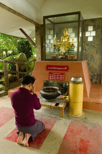 2019-11-06 / Phuket, Thailand - A kneeling, bare-footed man praying to a golden statue of Buddha.
