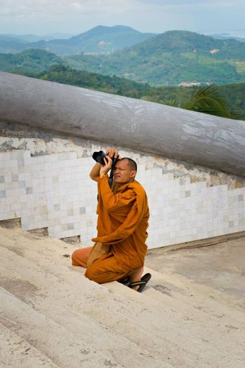 2019-11-06 / Phuket, Thailand - A buddhing monk in saffron robes kneels down to take a picture with a DSLR camera.