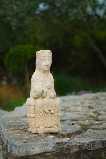 Small medieval sculpture of Virgin Mary holding a baby Jesus Christ. Early medieval style replica.