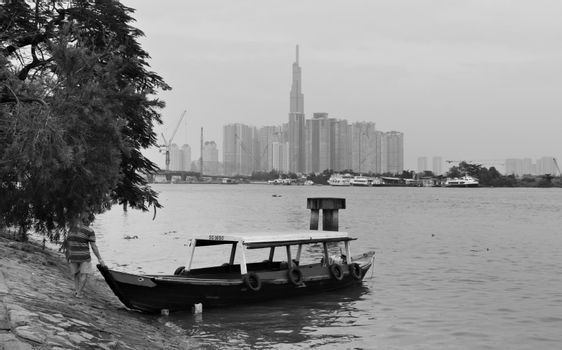 2019-11-10 / Ho Chi Minh City, Vietnam - A poor man pushes a boat into the river, with tall, modern skyscrapers in the background.