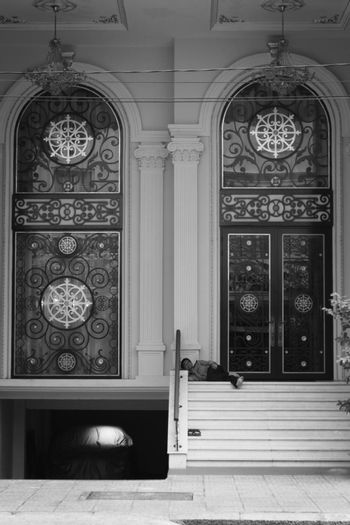 2019-11-10 / Ho Chi Minh City, Vietnam - A poor, barefoot man sleeping in the entrance floor of a fancy, luxury buliding.