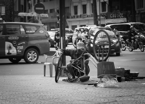2019-11-12 / Ho Chi Minh CIty, Vietnam - A man repairing an old bicyle on a sidewalk. Black and white.