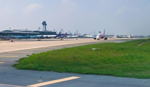 2019-11-14 / Ho Chi Minh City, Vietnam - Airliners queue up in the taxiway of the airport, awaiting authorization to take off.
